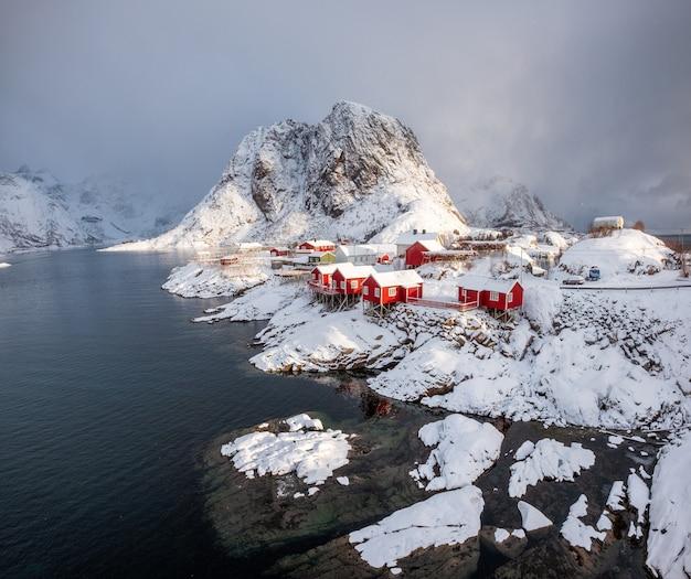 Villaggio di pescatori della casa rossa con la montagna della neve nel giorno delle precipitazioni nevose