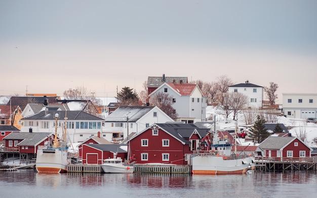 Villaggio norvegese con peschereccio sulla costa in inverno