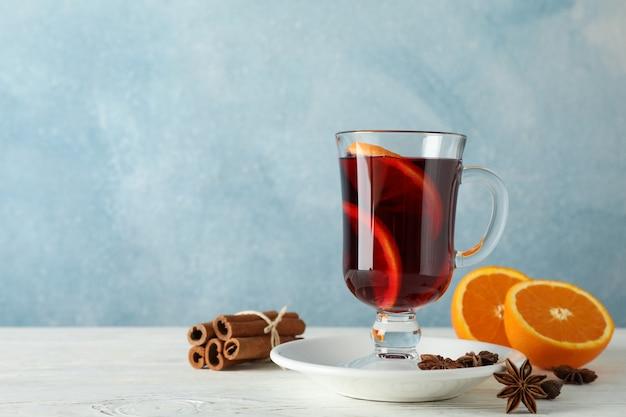 Vin brulé, arancia e cannella sulla tavola di legno bianca