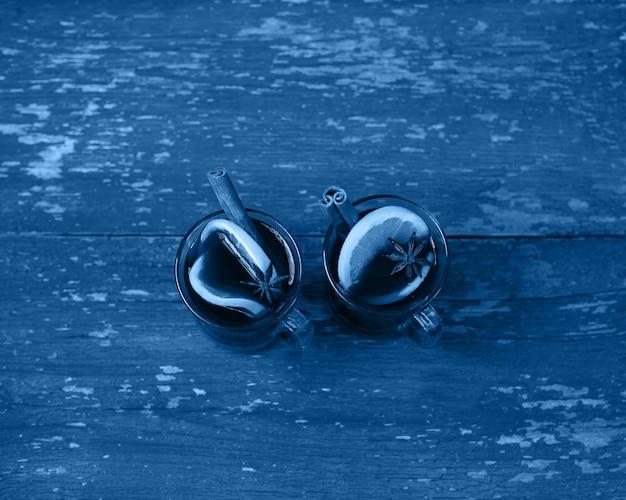 Vin brulé caldo di natale con cardamomo e anice di cannella su fondo di legno blu