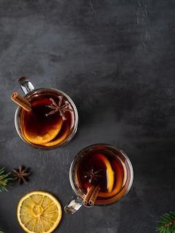 Vin brulè con fettine di arancia, anice stellato, spezie e bastoncini di cannella su sfondo scuro con rami di abete rosso. layout piatto di natale e capodanno. bevande vista dall'alto.