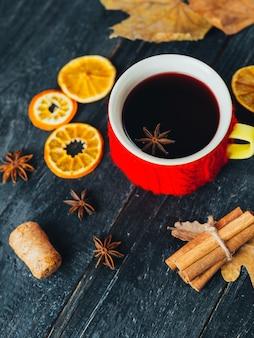 Vin brulè con spezie e arancia su fondo in legno con foglie di autunno