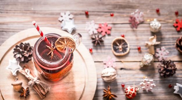 Vin brulè con spezie e fiocchi di neve in legno
