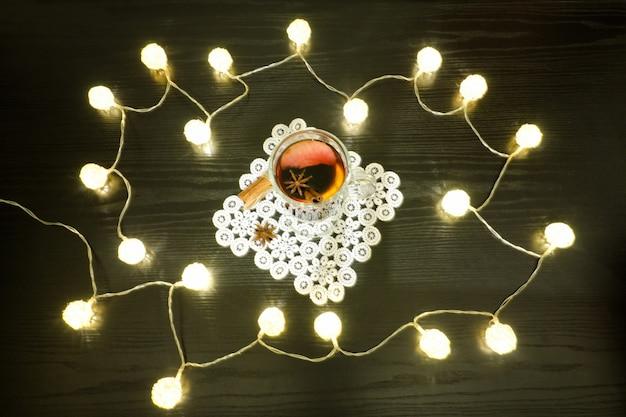 Vin brulè con spezie su un tovagliolo di pizzo e cannella. lanterne in rattan sul tavolo di legno nero