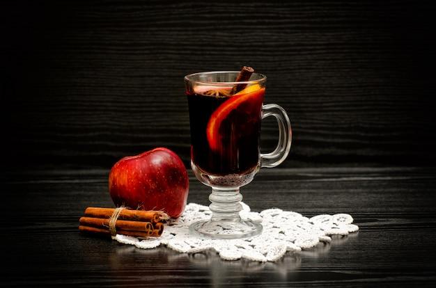 Vin brulè con spezie su un tovagliolo di pizzo, mela e bastoncini di cannella. legno nero sullo sfondo