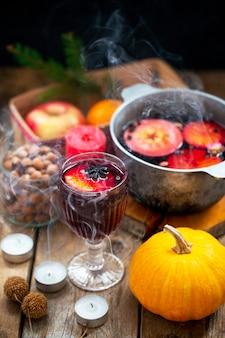 Vin brulé del vino rosso di natale con le spezie e la frutta su una tavola rustica di legno. bevanda calda tradizionale per natale. bevanda calda al vin brulè con agrumi, mele e spezie in padella.