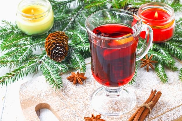 Vin brulè di capodanno in un bicchiere sullo sfondo di ramoscelli, candele e ghirlande.