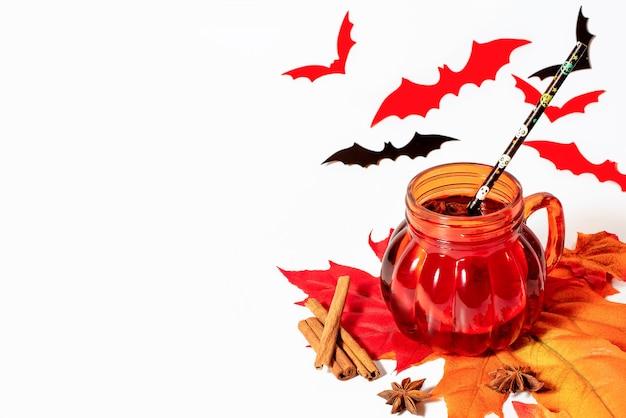Vin brulè di halloween in tazza a forma di zucca con spezie su sfondo bianco.