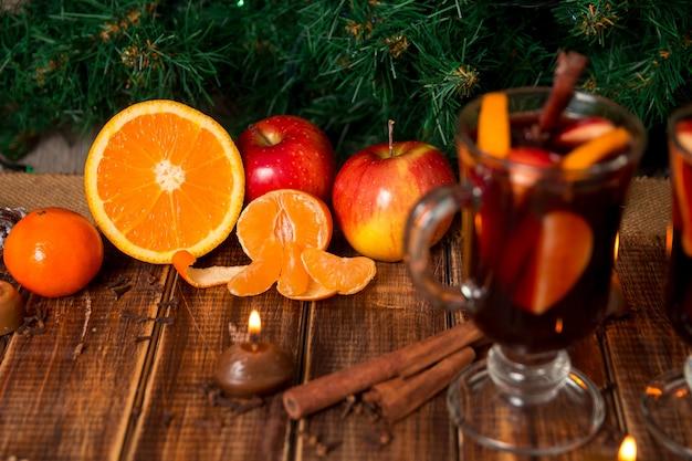 Vin brulé di natale con frutta e spezie sul tavolo di legno. decorazioni di natale in background.