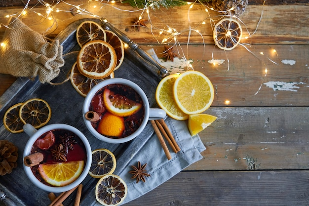 Vin brulè di natale in due tazze rustiche con frutta e spezie sul tavolo di legno
