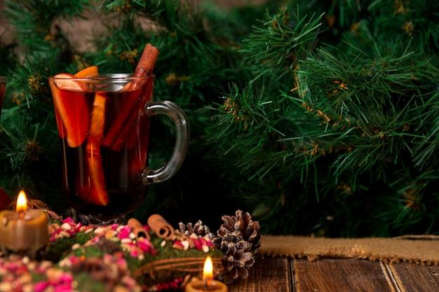 Vin brulé e stella di natale, candele sulla tavola di legno. decorazioni di natale in background.