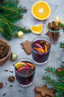 Vin brulè in un bicchiere con arancia, mela, uva passa, cannella, anice stellato e altre spezie su una superficie grigia con pan di zenzero