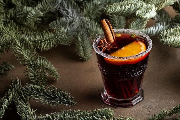 Vin brulè in un bicchiere con bastoncini di cannella e spezie di anice stellato circondato da rami di abete su un tavolo marrone