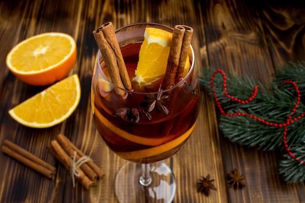 Vin brulè nel bicchiere sul tavolo di legno marrone