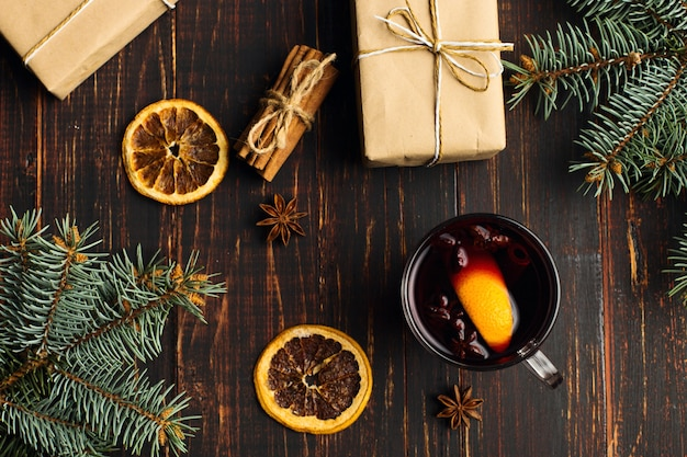 Vin brulè, un regalo e spezie sul tavolo accanto all'albero