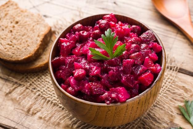 Vinaigrette di insalata di barbabietole fatta in casa fresca in una ciotola di legno. cibo tradizionale russo.