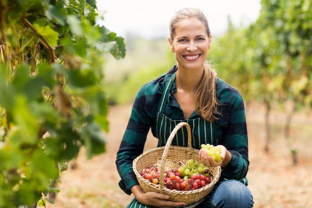 Vinaio femminile felice che tiene un cestino dell'uva