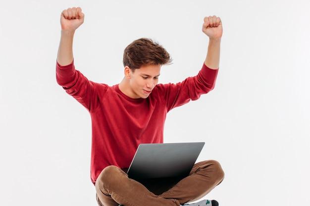Vincere felice del giovane al computer portatile su fondo bianco