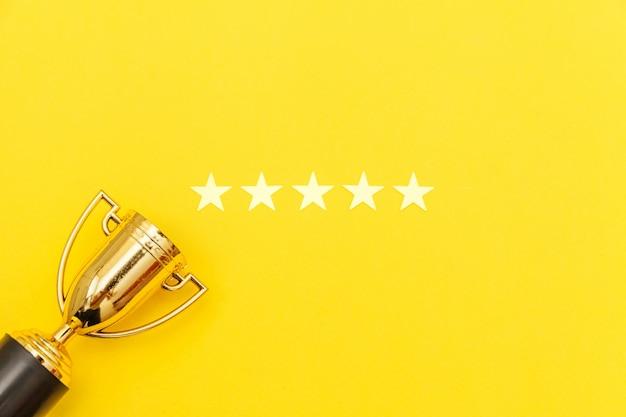 Vincitore del design semplicemente piatto o campione coppa d'oro trofeo e 5 stelle valutazione isolato su sfondo rosa pastello. vittoria primo posto di competizione. concetto vincente o di successo. vista dall'alto copia spazio.