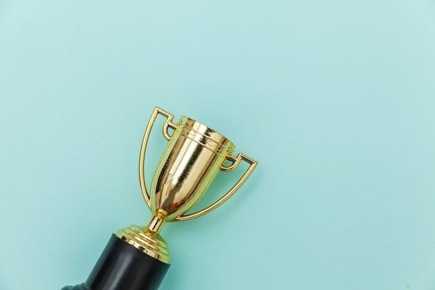 Vincitore o campione coppa trofeo d'oro isolato su sfondo colorato pastello blu