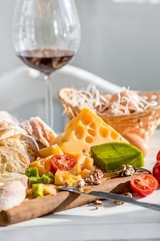 Vino, baguette e formaggio su di legno