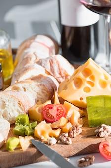 Vino, baguette e formaggio sulla tavola di legno
