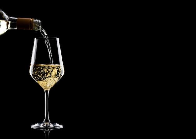 Vino bianco di versamento dalla bottiglia a vetro isolato