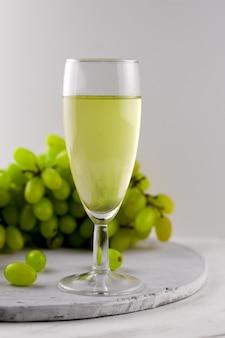 Vino bianco e uva su uno sfondo di marmo