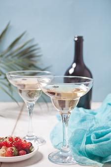 Vino bianco in bicchieri, bottiglia e piatto con bacche sul tavolo di legno bianco. cena per due.