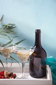 Vino bianco in bicchieri, bottiglia e piatto con bacche sul vassoio di legno bianco. cena per due.