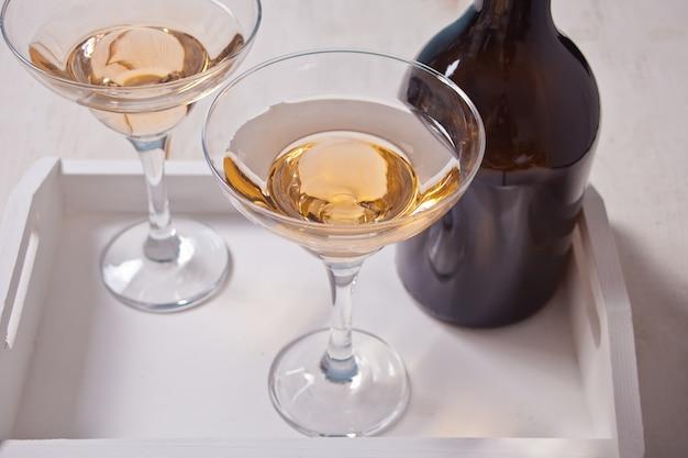 Vino bianco in bicchieri, bottiglia sul vassoio di legno bianco. cena per due.