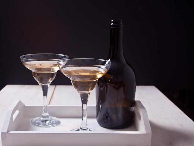 Vino bianco in bicchieri, bottiglia sul vassoio di legno bianco