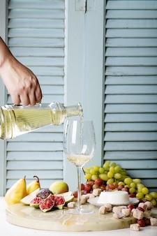 Vino bianco in un bicchiere servito con frutta fresca
