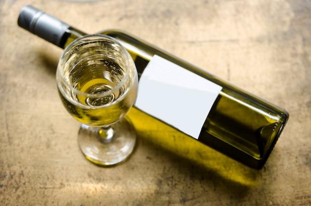 Vino bianco in vetro e bottiglia sul tavolo rustico dorato