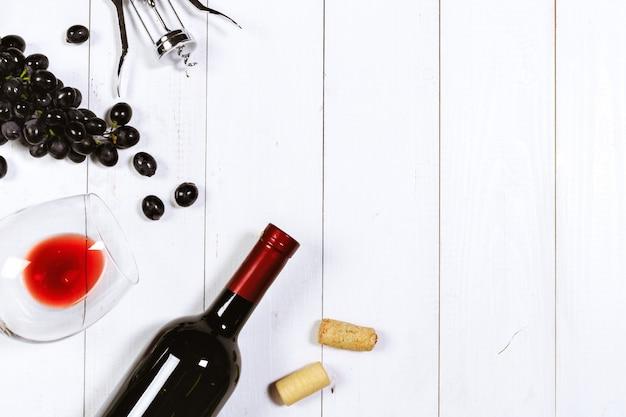 Vino con rami di uva bianca. su un tavolo di legno.