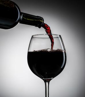Vino d'uva versato dalla bottiglia in bicchiere da vino in vetro