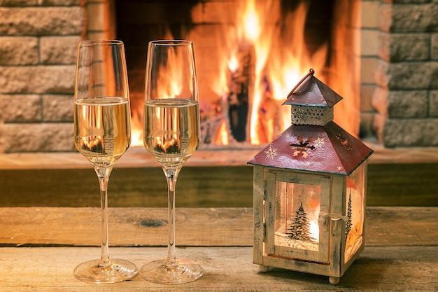 Vino di champagne in bicchieri vicino al caminetto