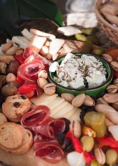 Vino e snack set varietà di formaggi, olive su tavola rustica su uno sfondo naturale. vista da vicino. pasto italiano
