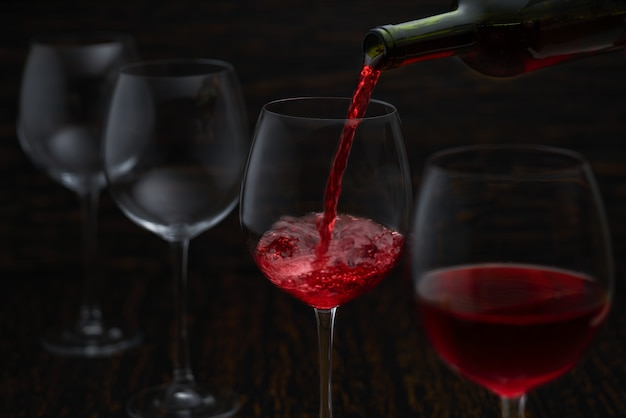 Vino rosso che versa nei bicchieri dalla bottiglia