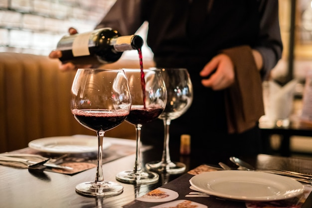Vino rosso che versa nel bicchiere di vino, close-up