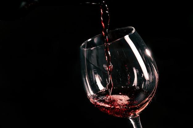 Vino rosso che versa nel bicchiere