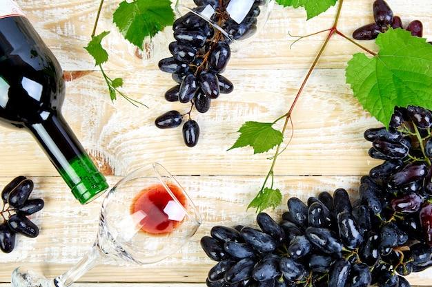 Vino rosso con bottiglia, bicchiere e uva.