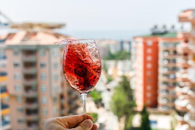 Vino rosso con cubetti di ghiaccio in un bicchiere su una vista esterna. vista laterale.