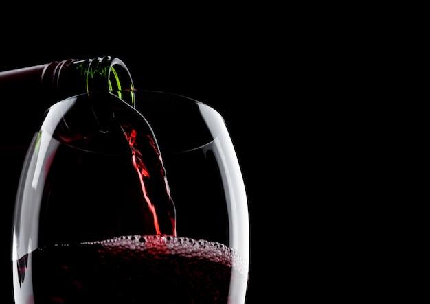 Vino rosso di versamento dalla bottiglia a vetro isolato