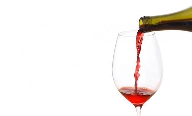 Vino rosso di versamento in vetro dalla bottiglia contro priorità bassa bianca