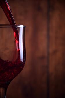 Vino rosso di versamento nel vetro contro il fondo rustico di legno