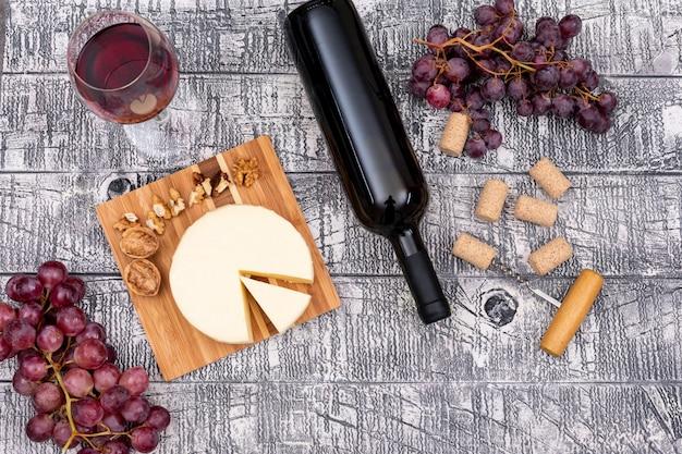 Vino rosso di vista superiore con l'uva e il formaggio a bordo e sull'orizzontale di legno bianco