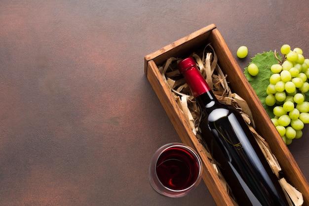 Vino rosso in una cassa e uve bianche