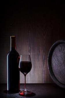 Vino rosso in vetro e bottiglia con botti e assi