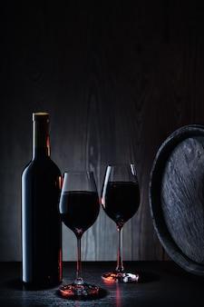 Vino rosso in vetro e bottiglia sullo sfondo di botti di legno e pareti
